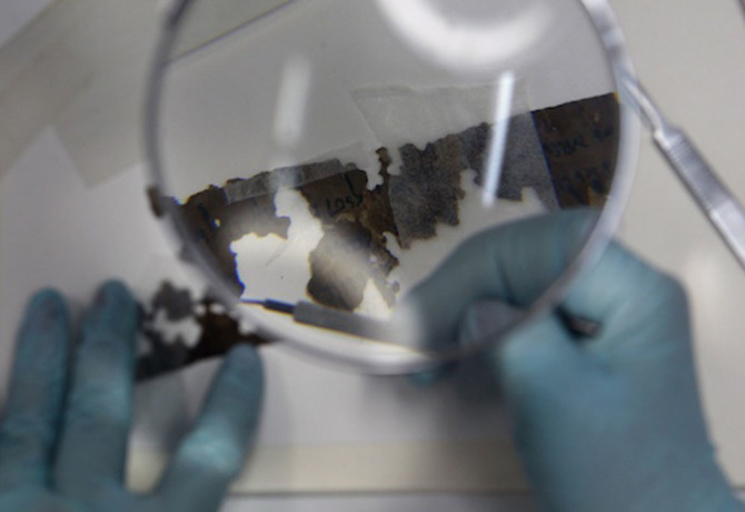 Preservationist works on a fragment of the Dead Sea Scrolls in the Israel Museum in Jerusalem