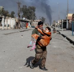 an-iraqi-special-forces-soldier-carries-a-woman-injured-during-a-battle-between-iraqi-forces-and-islamic-state